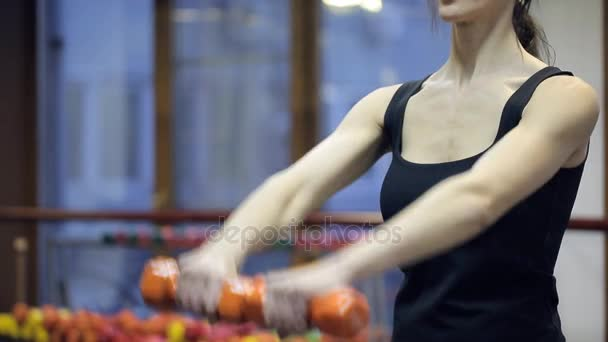 Woman standing training chest, arms muscles with dumbbells indoors