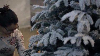 Žena množiny a příprava vánoční strom zdobí místnost