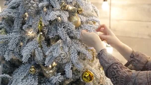 somebody tie gold ribbon from organza as decoration to christmas tree stock video