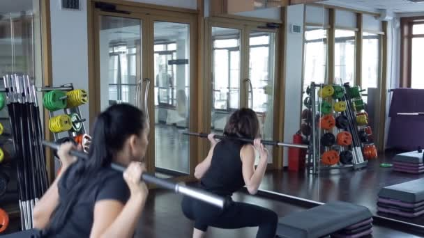 two women raising bar on shoulders inside sport gym