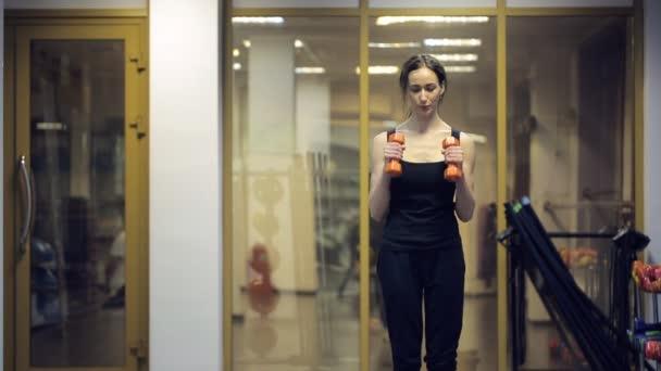 Žena vlaky squatu s činkami před kamerou uvnitř tělocvičny