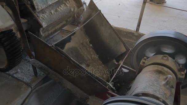 Zblízka ukazuje mechanismus, jímž nalil štěrk v továrně