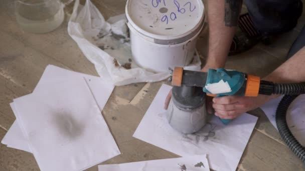 Malíř na dřevěné podlaze provozuje malou láhev pro zbraň