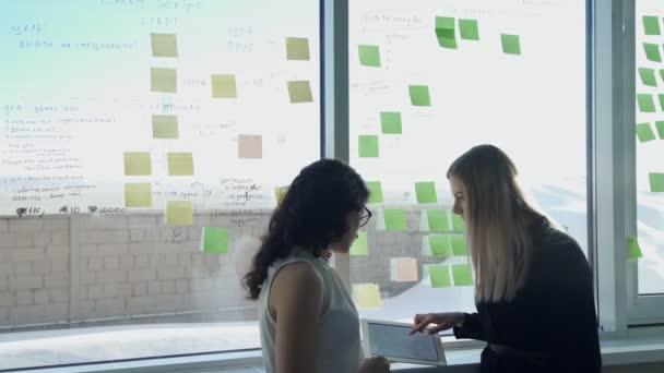 Dvě ženy podnikání na pozadí okna v hale diskutovat na různá témata