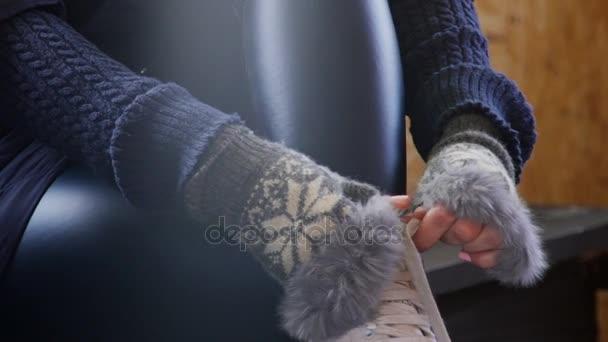 Žena v Teplý svetr a rukavice zakotvuje bílé brusle
