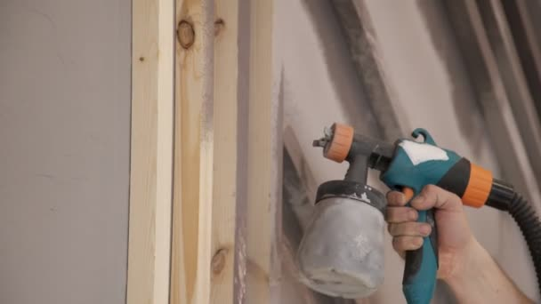 close-up of worker hand using spray gun and painting wood in house