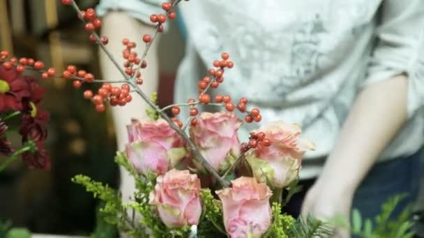 florists makes floral arrangement on table inside store