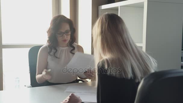 Der Chef gibt der Frau bei der Einstellung die Unterschrift unter den Arbeitsvertrag.