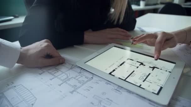 Dvě ženy a muž diskutovat o Architektonický projekt v kanceláři pomocí přenosného počítače.