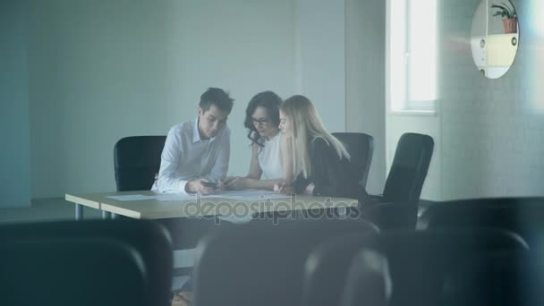 V prázdné konferenční místnosti tři zaměstnanci pracují přesčas pro papíry