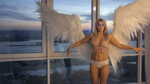 Photosession blonde model with white wings inside photo studio