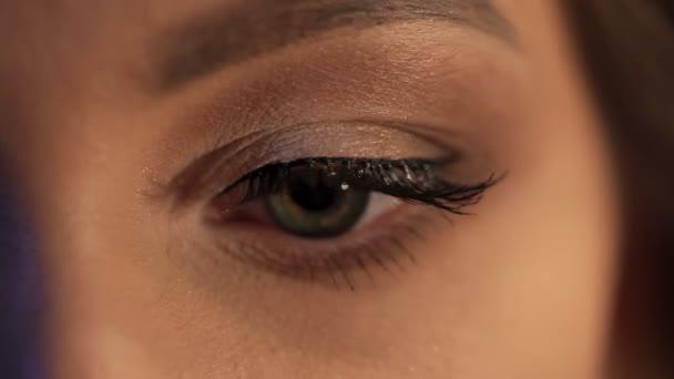 Closeup Střelba na zelené oko mladé ženy, rozhlédl se kolem sebe