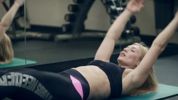 Female athlete doing abdominal crunches lying on floor in gym.