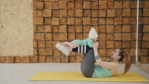 Young woman doing abdominal crunches lying on floor holding baby indoors.