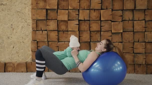 Fitness lady does abdominal crunches on gymnastic ball holding child indoors.