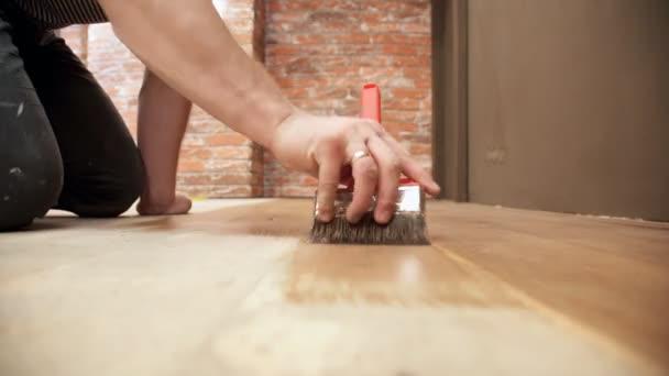 Jonge man doen reparaties schilderen houten vloer binnenshuis