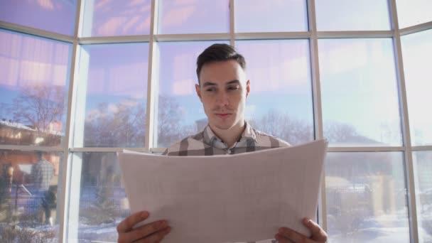 Mladý architekt se dívá na schémata stoje v úřadu