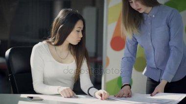4k: zwei weibliche Angestellte in einem Büro zusammenarbeiten. Die ...