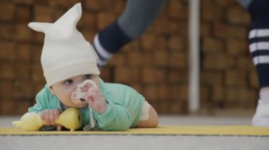 During a fitness session, a small child gnaws a childs toy.