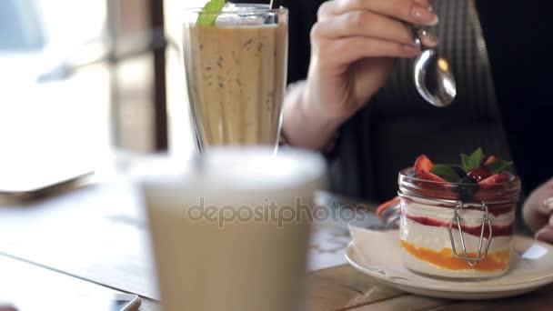 eine Frau mit luxuriösem Armband probiert ein Dessert mit Beeren.