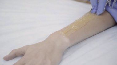 Close-up shooting of woman hand, master smears hot wax on skin