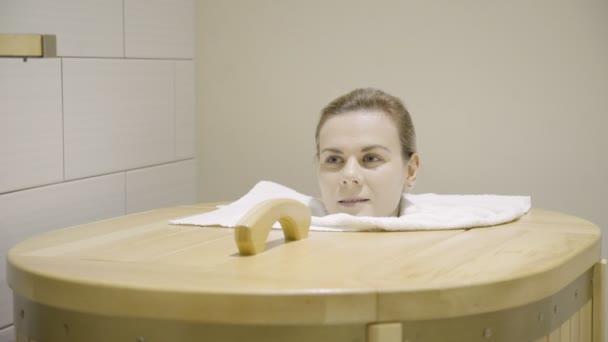 Žena sedí v sauně, konstrukce hlavy s vysokou teplotou ve spa salonu