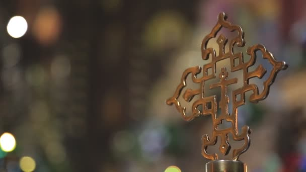 Golden religious cross on background of the lights in church.