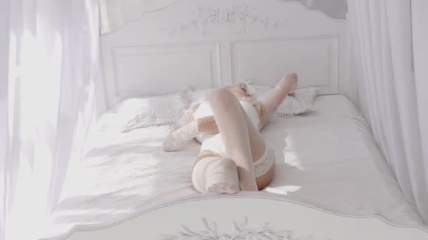Sexy Frau in weißen Spitzenunterwäsche bewegt sich langsam im Bett