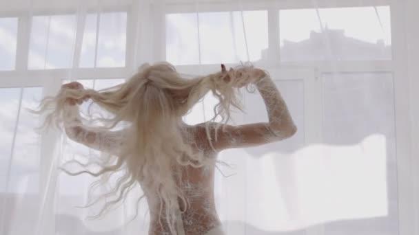 Nő fehér fehérnemű ablakon kenhető hosszú szőke haj.
