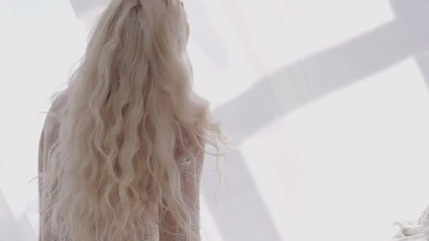 Blonde in lace underwear twist her long curly hair around.