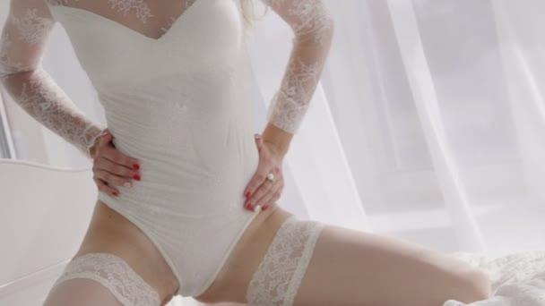 Sexy Frau in weißen Strümpfen und lacy Dessous auf dem Bett kniend