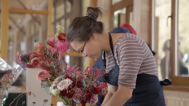 Květinářství žena v zástěře zdobí kytice s flitry pro událost