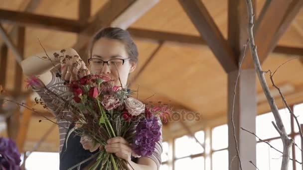 Talented florist creates floral bouquet, standing indoors.