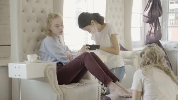 Mladá žena zasedání manikúra a pedikúra v salonu krásy