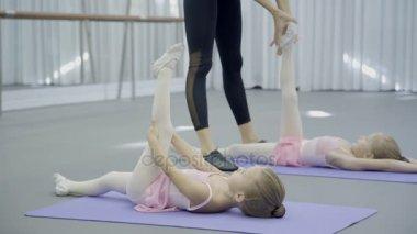 In ballet studio teacher trains socks on feet of children in shoes.