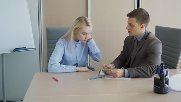 Mann und Frau reden mit Smartphone im modernen Büro.