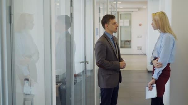 A férfi vezetője találkozik új női kollégája, a világos office folyosón.