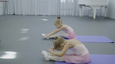 Two little girls in dance costumes are sitting and doing exercises.