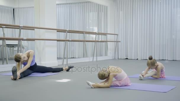 A balett stúdió női edző azt mutatja, a fiatal lányok lejtőin ülő.