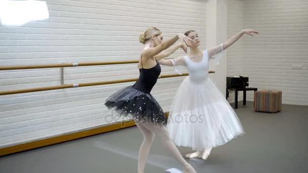 Two beautiful ballerinas rehearse dance in ballet studio.