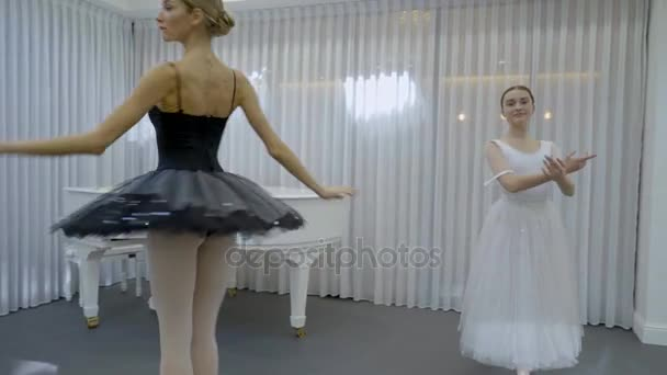 Two prima ballerinas have a repetition on the bright class with the grand piano in the corner.