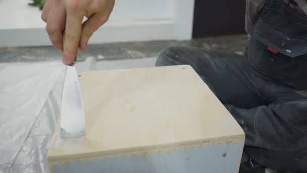 Opravář pokrývá místo šroubů s stavební tmel na zásuvku.