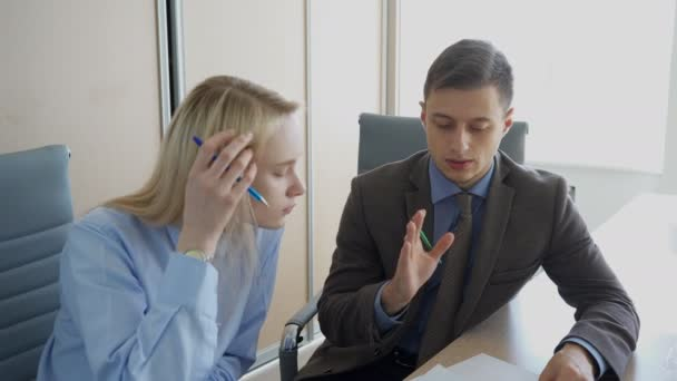 The businessman is giving a feedback to young female manager in his office.