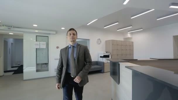 Mladý podnikatel hledá pokoj k pronajmutí v moderní kancelářské budovy a sekretářka mu pomáhá.