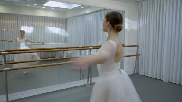 The young ballerina trains to do fouette in front of the mirror with barre in bright ballet class.