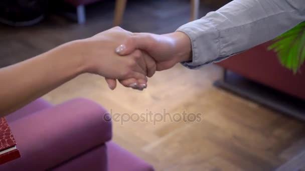 Dvě obchodní ženy shovívavě potřást rukou před schůzkou.