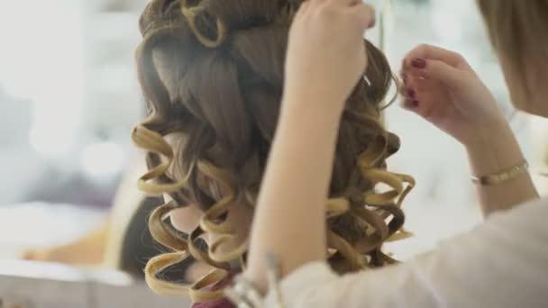 Kadeřník dělá kadeře za ženy a umělce platí make-up na obličej.