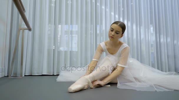 die junge Ballerina bindet ihre spitzen Zehen auf dem Boden im hellen Atelier.