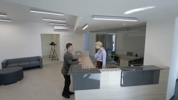 Uomo daffari sta parlando con bionda segretaria femminile alla