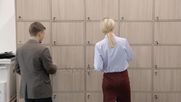 Man and woman open boxes and pick up things in modern office.